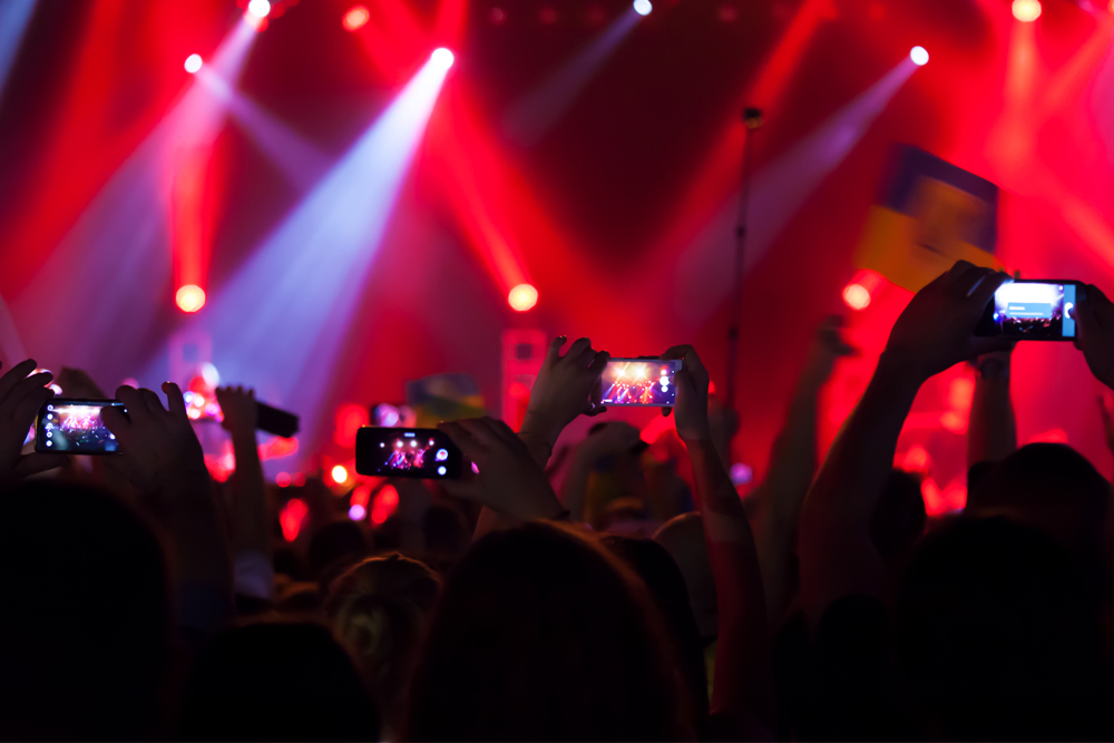 people taking video of a concert